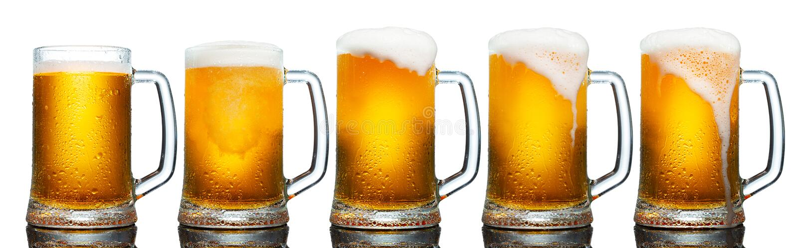 Set of mugs of cold light beer with foam isolated on white background. Set of mugs of cold light beer with foam isolated on white background royalty free stock image