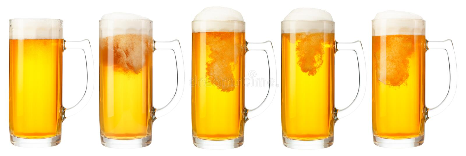 Set of mugs of cold light beer with foam isolated on white background. Set of mugs of cold light beer with foam isolated on white background royalty free stock photography