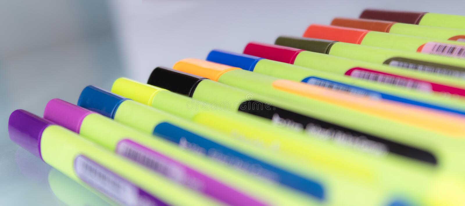 A set of multi-colored markers located on the glass with blur foreground royalty free stock photography