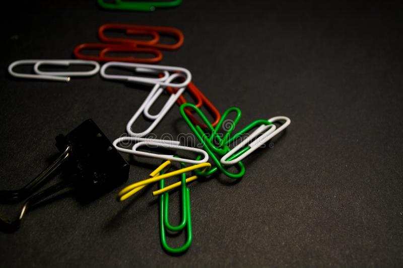 A set of multi-colored office paper clips of plastic are scattered on black monophonic background. A set of multi-colored office paper clips of plastic are stock images