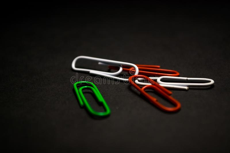 A set of multi-colored office paper clips of plastic are scattered on black monophonic background. A set of multi-colored office paper clips of plastic are royalty free stock images