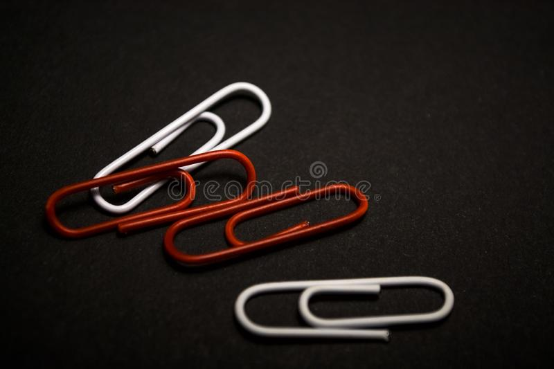 A set of multi-colored office paper clips of plastic are scattered on black monophonic background. A set of multi-colored office paper clips of plastic are stock photo
