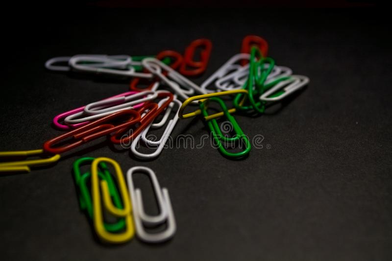 A set of multi-colored office paper clips of plastic are scattered on black monophonic background. A set of multi-colored office paper clips of plastic are stock image