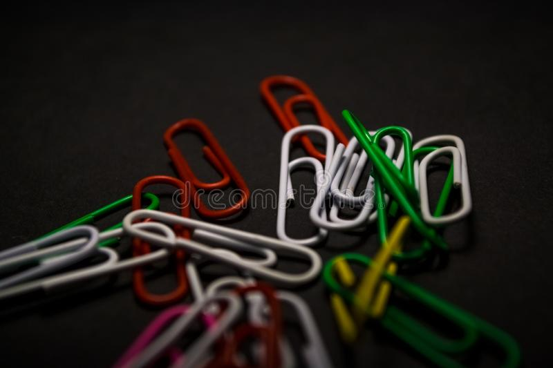 A set of multi-colored office paper clips of plastic are scattered on black monophonic background. A set of multi-colored office paper clips of plastic are royalty free stock image