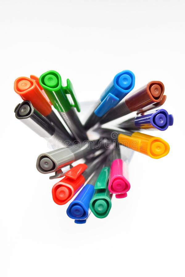 Set of multi-colored pens standing in a transparent glass, top view on white background, , vertically oriented. Set of multi-colored pens standing in a stock photos