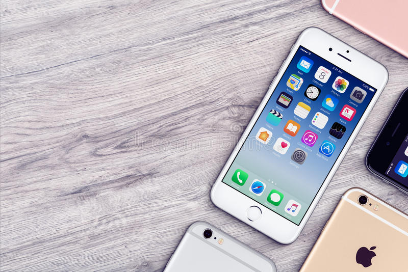 Set of multicolored Apple iPhones 6s flat lay top view lies on wooden office desk with copy space stock photo