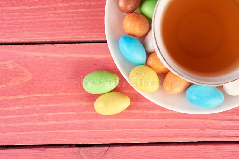 Set of multicolored dragee with cup of tea on pink background stock image