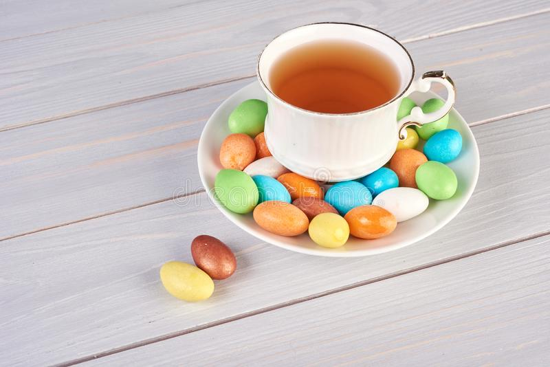 Set of multicolored dragee with cup of tea on white background royalty free stock image