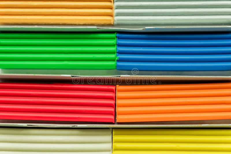Set of multicolored plasticine bars for modeling on wooden table stock image
