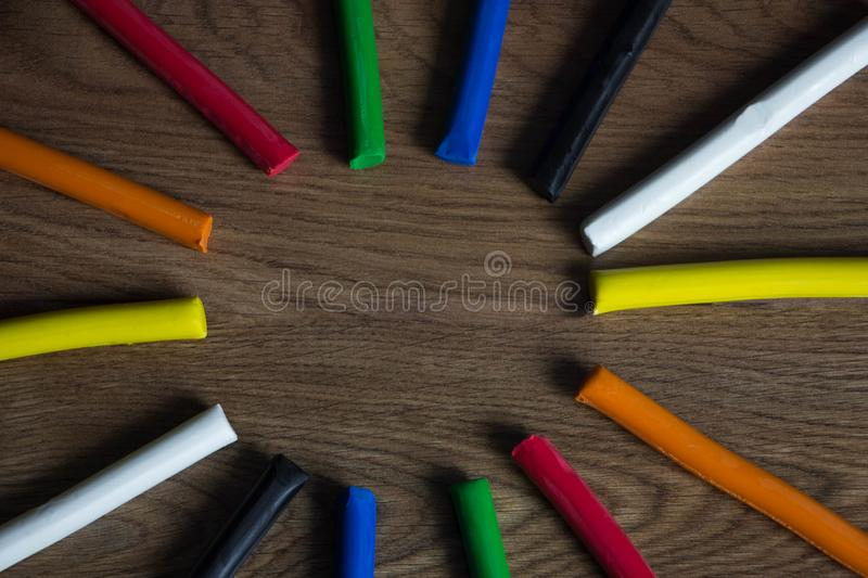 Set of multicolored plasticine bars for modeling on wooden table. Top view, eduction and creativity concept royalty free stock photography