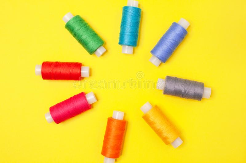 Set of multicolored spools of thread on yellow background. Accessories for needlework, embroidery, sewing. Flat lay. Top view. royalty free stock images