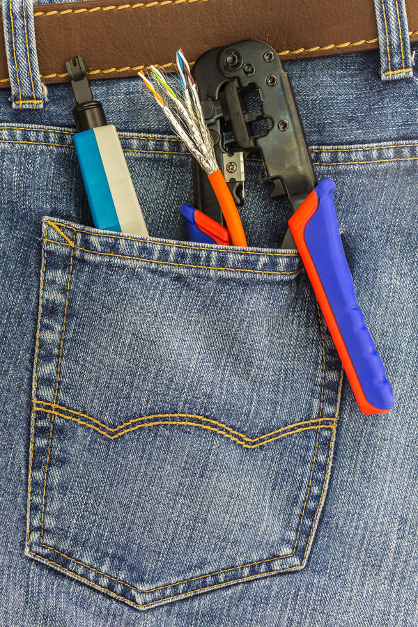 Set of network instruments in a back pocket of jeans. Set of network instruments in a back pocket of a blue denim jeans stock photo