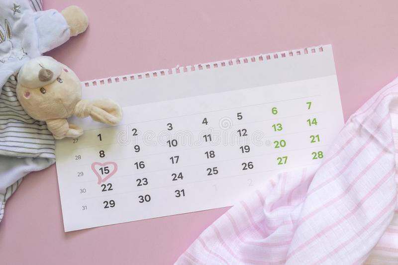 Set of newborn accessories in anticipation of  child - calendar with circled number 15 fifteen, baby clothes, toys on pink stock photography