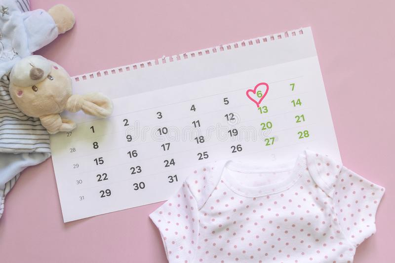 Set of newborn accessories in anticipation of  child - calendar with circled number 6 six, baby clothes, toys on pink background. Copy space, flat lay, top stock photos