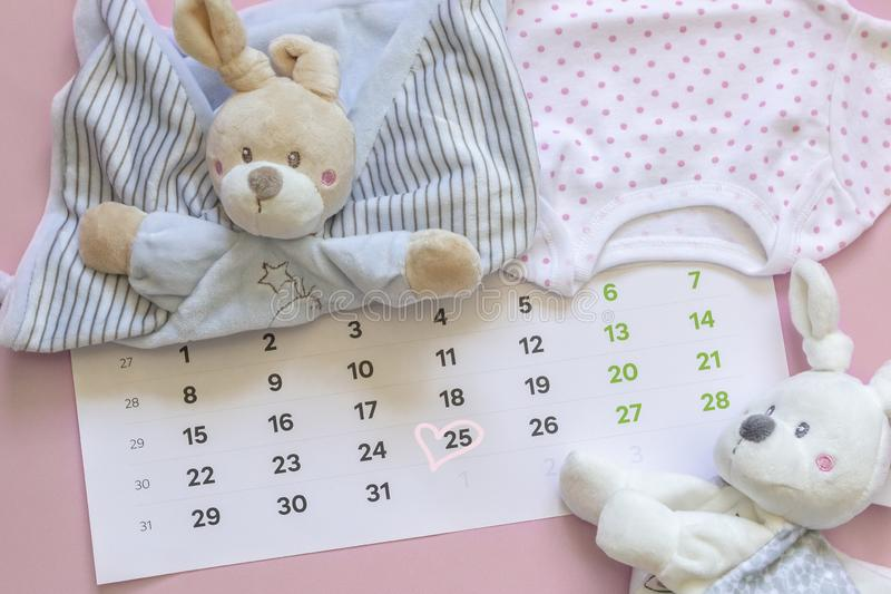 Set of newborn accessories in anticipation of  child - calendar with circled number 25 twenty five, baby clothes, toys on pink. Background. Flat lay, top view royalty free stock images