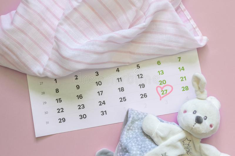 Set of newborn accessories in anticipation of  child - calendar with circled number 27 twenty seven, baby clothes, toys on pink. Background. Flat lay, top view royalty free stock photography
