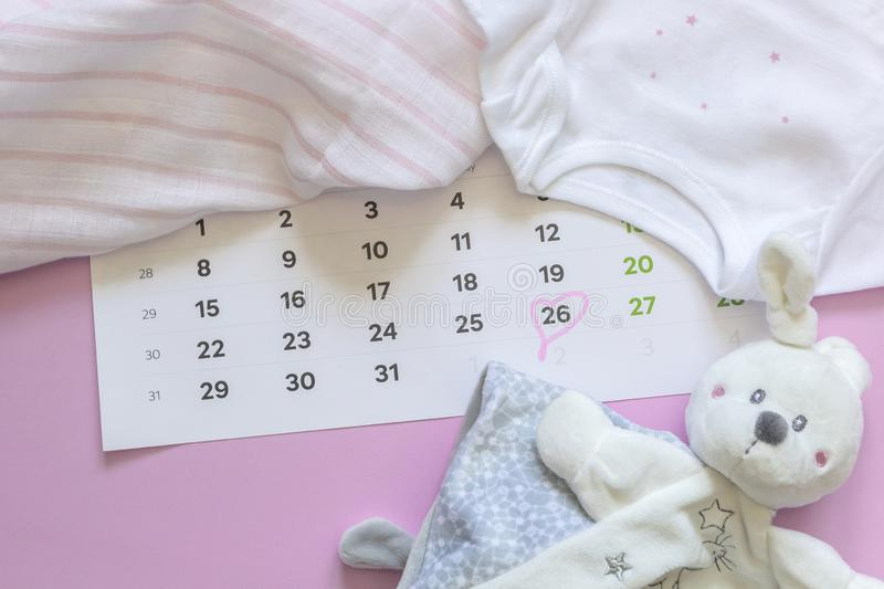 Set of newborn accessories in anticipation of  child - calendar with circled number 26 twenty six, baby clothes, toys on pink. Background. Flat lay, top view stock image