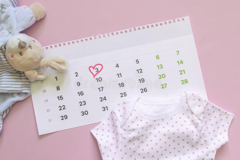 Set nowonarodzeni akcesoria w oczekiwaniu na dziecko - kalendarz z okr??aj?c? liczb? 3 trzy dziecka ubrania, zabawki na menchiach zdjęcie stock