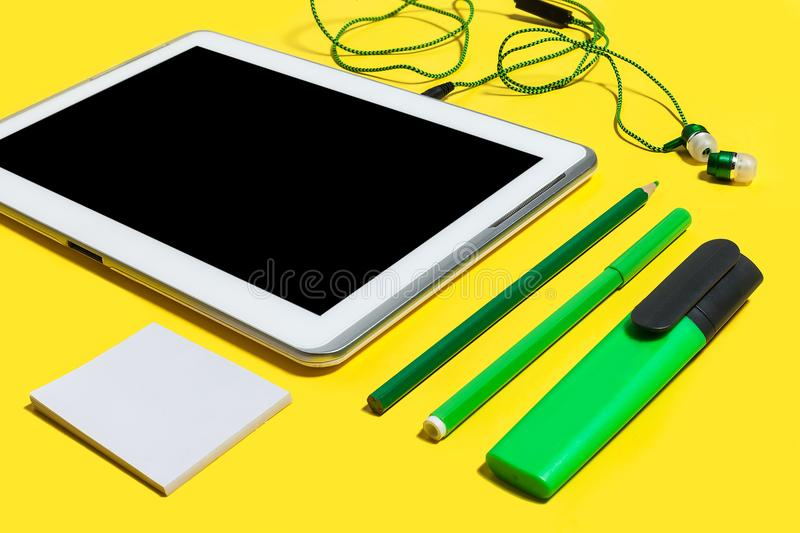 Set of office stationary and gadgets. Set of business or education accessories. green pencils, headphones, paper stickers, markers and tablet pc lying on a stock photo