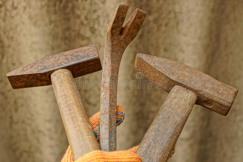 Two old brown hammers and a steel rusty hammer in hand stock photo