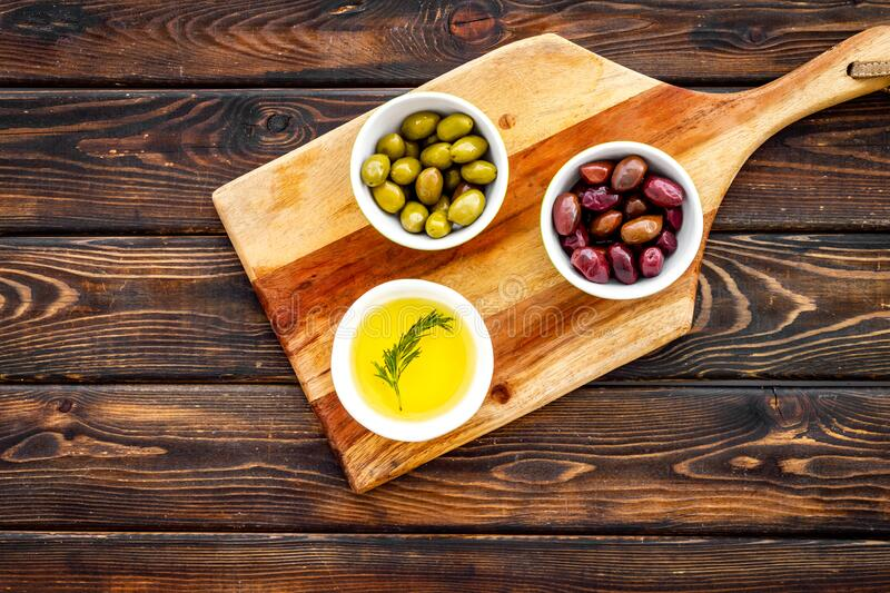 Set of olives with oil on kitchen table. Top view royalty free stock photo