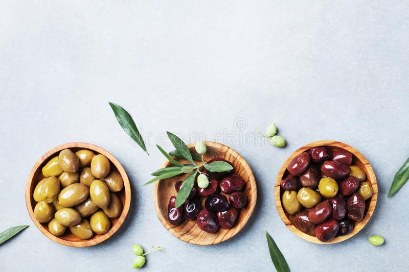 Set from olives in wooden bowls decorated with fresh olive tree branch top view. stock photography