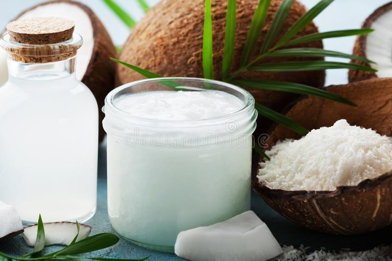 Set of organic coconut products for spa, cosmetic or food ingredients decorated palm leaves. Natural oil, water and shavings. royalty free stock photos