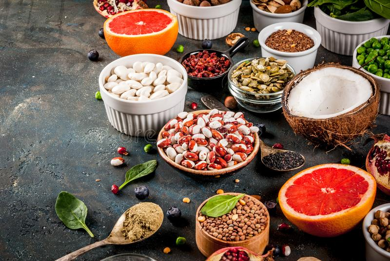 Set of organic healthy diet food, superfoods - beans, legumes, n. Uts, seeds, greens, fruit and vegetables. Dark blue background copy space stock image