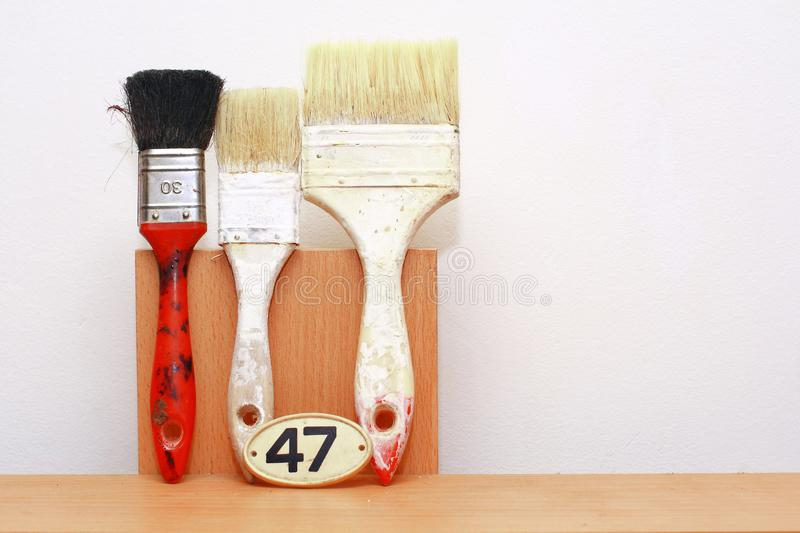 Set of paint brushes against wall royalty free stock photo