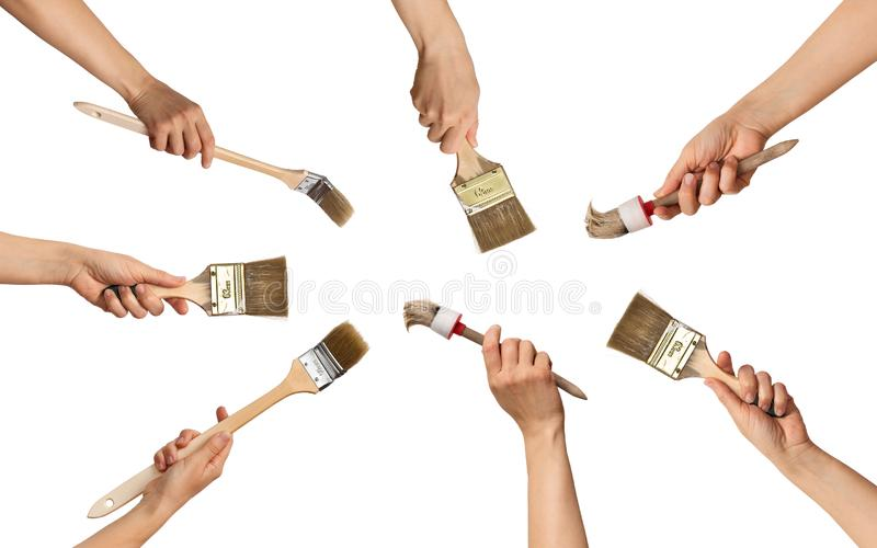 Set of paint brushes in hands in a circle royalty free stock photo