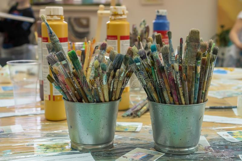 Set of paintbrushes multi-colored on the cup. Paint brushes and paints for drawing. Interior of the art school for drawing stock photography