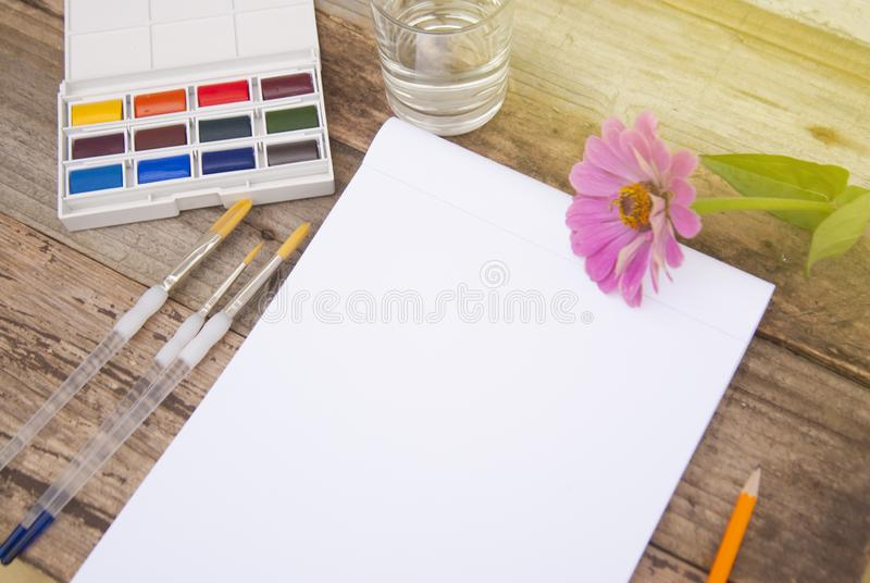 Set of paints, pencils, tools for painting and blank white paper sheet of sketchbook on rustic wooden background. Top stock images