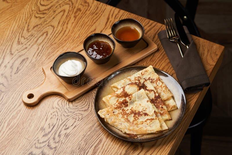 Homemade pancakes with jam, honey and sour cream bowls, close-up royalty free stock photos