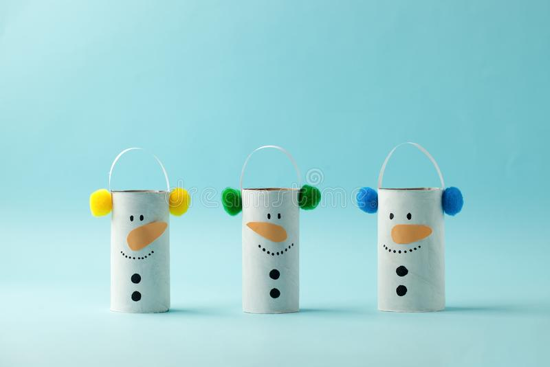 Set Paper Snowmen for Happy new year Merry Christmas party. Easy craft for kids on blue background, simple diy idea from toilet. Rool tube, recycle concept stock photo