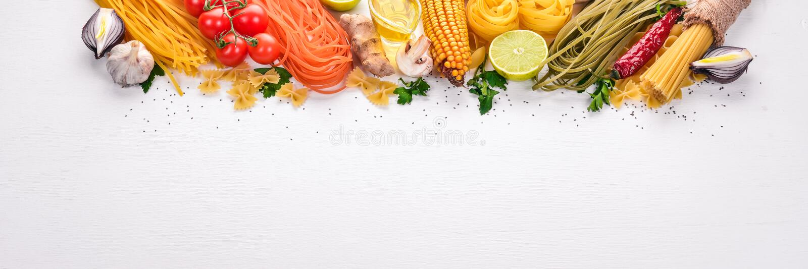 Set of pasta, noodles, spaghetti. Italian cooking, fresh vegetables and spices. On a white background. Top view. Copy space royalty free stock photography