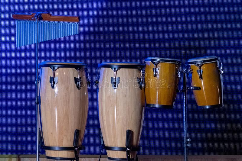 A set of percussion instruments. Conga - Cuban drums on the racks. Musical theme. Blue background royalty free stock photo