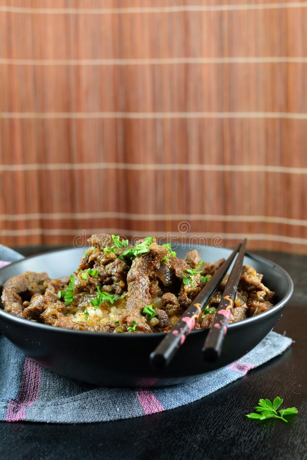 Beef Stir Fry with Rice. A set of photos showing a bowl of beef stir fry with cooked rice. Served in a bowl on black background royalty free stock photos