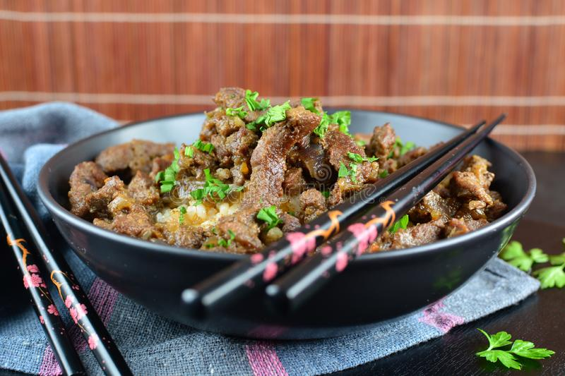 Beef Stir Fry with Rice. A set of photos showing a bowl of beef stir fry with cooked rice. Served in a bowl on black background stock photos