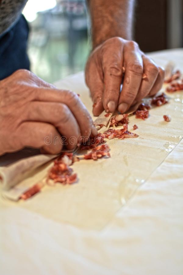 An old man preparing a traditional Mediterranean meat pie stock photos