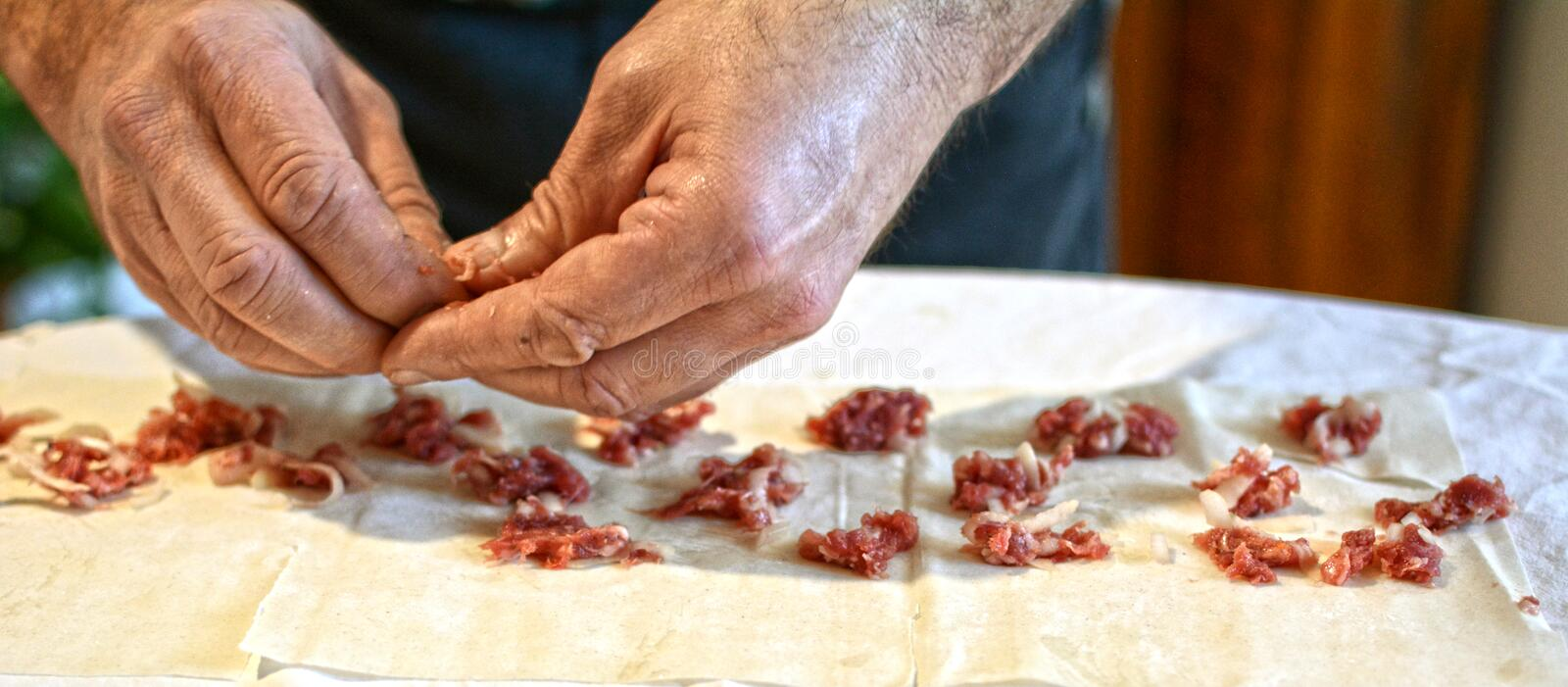An old man preparing a traditional Mediterranean meat pie stock image