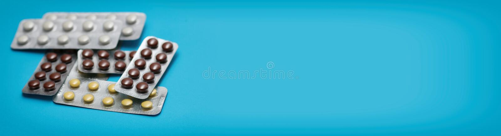 Set of pills blisters on blue solid background. Long banner photo. Header format. Place for your information text. Medical concept. Online shop of supplements royalty free stock image