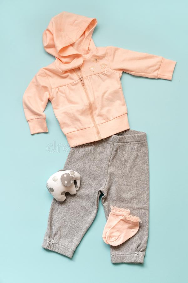 Set of pink children`s clothes on a blue background. Twist with a hood, gray pants, socks and an elephant`s toy. royalty free stock photos