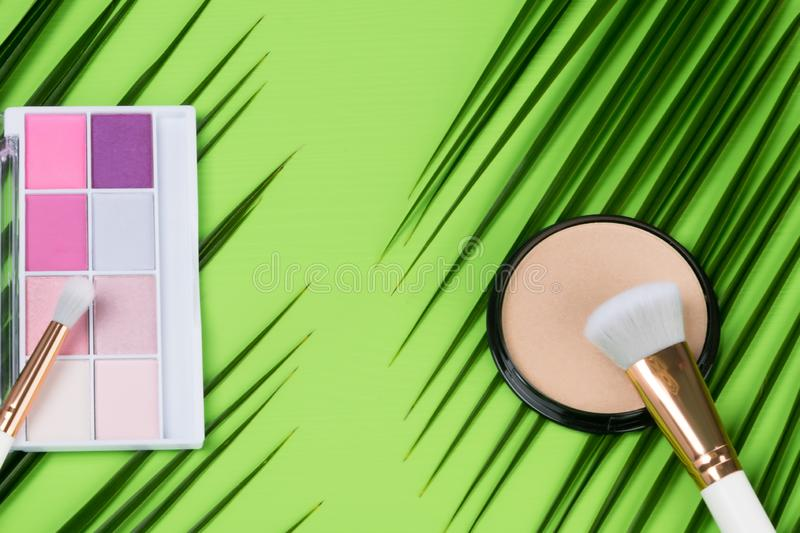 Set of pink eyeshadows and blush with a brush on a green background. Set of pink eyeshadows and blush  with a brush on a green background stock photos