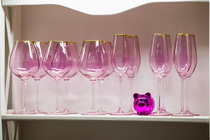 A set of pink glasses with a gold rim, beautiful wine glasses of modern design to decorate a wedding feast and holidays royalty free stock images