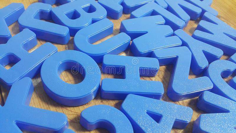 Set of plastic alphabet letters placed on a wooden floor royalty free stock photo
