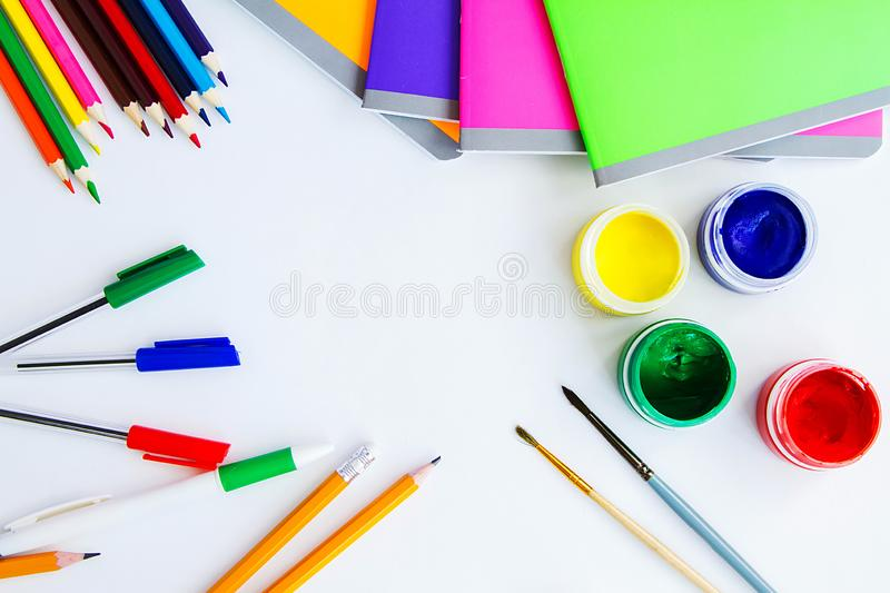 Set of plastic cans with colored paints, brushes, pencils, pens and colored notebooks on white background. royalty free stock photography
