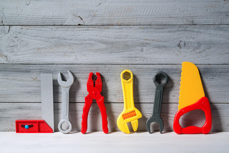 Set of plastic toy tools for children in a line on a wooden background. Set of colored plastic toy tools for children in a line on a wooden background royalty free stock photo