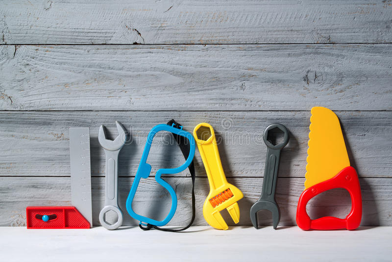 Set of plastic toy tools for children on a wooden background. Set of colored plastic toy tools for children on a wooden background royalty free stock photography