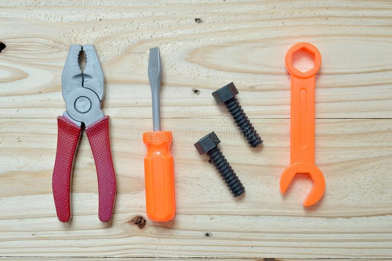 Set of plastic toy tools over wooden. Background stock photo