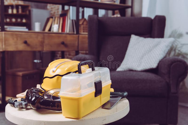Set of plastic toy tools and yellow toolbox on a table stock image